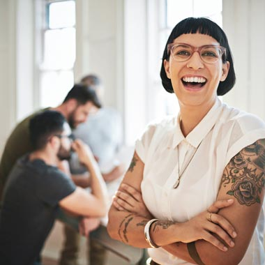 Woman smiling at camera with work colleagues in background working