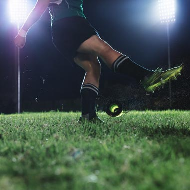rugby player kicking a ball on pitch at night with spotlight on