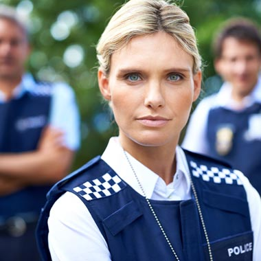 Female police officer looking at camera with two male officers behind blurred