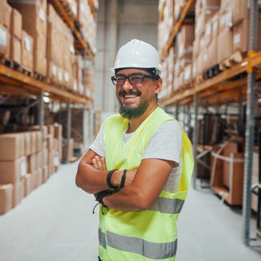 Man in hard hat and high vis vest in a warehouse smiling at camera