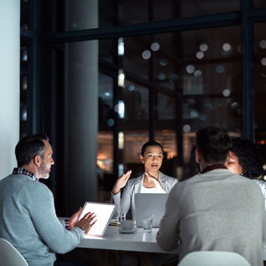 Four workers sitting around a table with laptops having a meeting in the evening