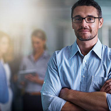 Office worker with arms crossed facing camera with colleagues in background