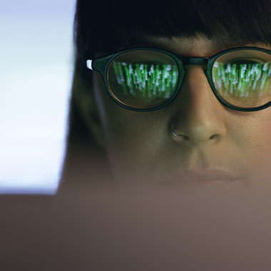 Close up of woman's face wearing glasses looking at a screen